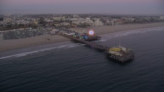 AX69_047 - 5K stock footage aerial video approach Santa Monica Pier at twilight and tilt to a bird's eye view, California