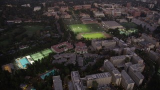 AX69_055 - 5K stock footage aerial video orbit College sports fields and campus buildings at twilight, Westwood, California
