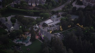 AX69_064 - Aerial stock footage of An orbit around The Playboy Mansion at twilight in Los Angeles, California