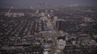 AX69_069 - 5K stock footage aerial video tilt from Wilshire Boulevard in Beverly Hills to reveal Downtown Los Angeles, California, twilight
