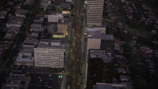 AX69_071 - 5K stock footage aerial video follow Wilshire Boulevard past office buildings in Beverly Hills, California, twilight