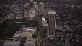 AX69_072 - 5K stock footage aerial video tilt from Wilshire Boulevard in Beverly Hills to reveal Downtown Los Angeles Skyline at twilight, California