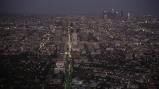 AX69_075 - 5K stock footage aerial video tilt from Wilshire Boulevard to reveal Koreatown and Downtown LA skyline at night, California