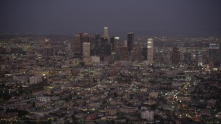 AX69_077 - 5K stock footage aerial video tilt from apartment buildings and city street to reveal Downtown Los Angeles skyline at night, California