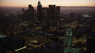AX69_085 - 5K stock footage aerial video orbit Los Angeles City Hall and reveal skyscrapers in Downtown Los Angeles at twilight, California