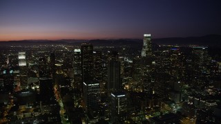 AX69_110 - 5K stock footage aerial video pan across Downtown Los Angeles skyscrapers at night, California
