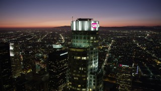 AX69_117 - 5K stock footage aerial video of orbiting top of US Bank Tower in Downtown Los Angeles at nighttime, California