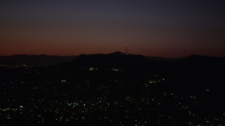 AX69_135 - 5K stock footage aerial video of radio tower and the lights of homes atop the Hollywood Hills at night, California