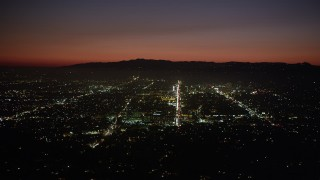 AX69_136 - 5K stock footage aerial video of bright lights of Hollywood streets at night, California