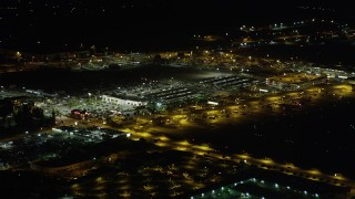 AX69_147 - 5K stock footage aerial video of a strip mall by Burbank Airport terminals at night in Burbank, California
