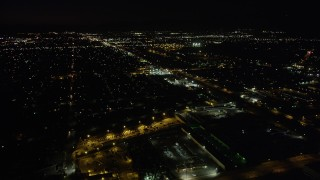 AX69_153 - 5K stock footage aerial video tilt to reveal suburban Pacoima neighborhoods and Whiteman Airport at night, California