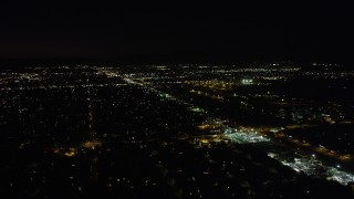 AX69_154 - 5K stock footage aerial video fly over neighborhoods and pan to Whitman Airport in Pacoima at night, California