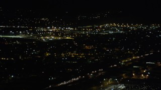 AX69_157 - 5K stock footage aerial video track small airplane flying over Pacoima homes at night, California