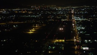 AX69_158 - 5K stock footage aerial video of small airplane landing at Whiteman Airport at night in Pacoima, California