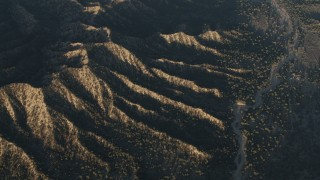 AX70_021 - 4K stock footage aerial video Dry riverbed by mountain ridges in Los Padres National Forest at sunrise, California