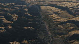 AX70_022 - 4K stock footage aerial video Dry riverbed between mountain ridges in Los Padres National Forest at sunrise, California