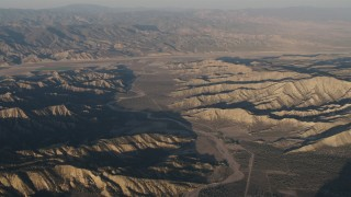AX70_026 - Aerial stock footage of 4K Aerial Video Dry riverbed between rugged mountain ridges at sunrise, Cuyama, California, farms in background