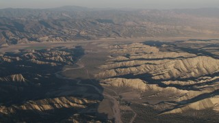 AX70_027 - Aerial stock footage of 4K Aerial Video Farms beyond a dry riverbed between rugged mountain ridges at sunrise, Cuyama, California