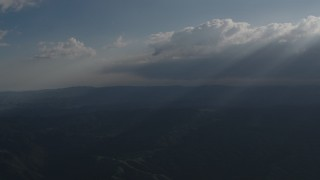 AX70_080 - 4K stock footage aerial video Rays of sunlight shining on mountains from the clouds over San Luis Obispo County, California