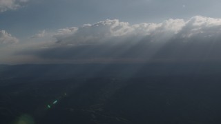 AX70_081 - 4K stock footage aerial video Rays of sunshine shining on mountains from clouds over San Luis Obispo County, California