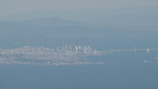 AX70_092 - 4K stock footage aerial video Downtown San Francisco and the Bay Bridge as a commercial jet flies over city, California