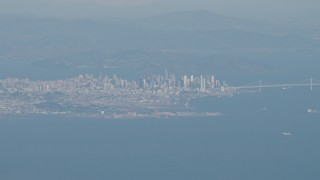 AX70_094 - 4K stock footage aerial video Downtown San Francisco, the Bay Bridge as a jet airliner passes, California