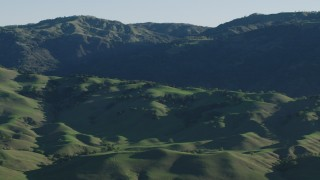 AX70_100 - 4K stock footage aerial video Green hills and mountains in springtime, Gilroy, California