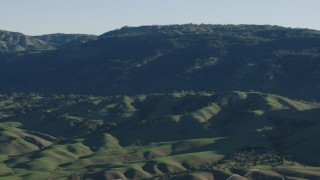 AX70_102 - 4K stock footage aerial video Flyby green hills beside mountains in springtime, Gilroy, California