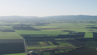 AX70_103 - 4K stock footage aerial video Fly over crop fields beside a country road in Hollister, California