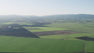 AX70_105 - 4K stock footage aerial video Flying over large crop fields in Hollister, California