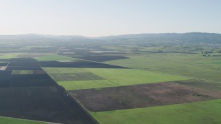 AX70_106 - 4K stock footage aerial video Flying over large crop fields to approach Bolsa Road in Hollister, California