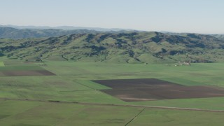 AX70_107 - 4K stock footage aerial video of farm fields and hills in Hollister, California