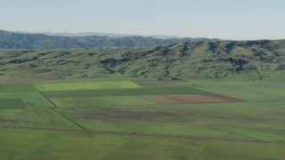 AX70_108 - 4K stock footage aerial video Farm fields beside green hills in Hollister, California