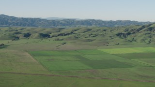 AX70_109 - 4K stock footage aerial video Flyby farm fields beside green hills in Hollister, California