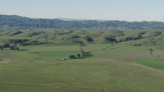 AX70_110 - 4K stock footage aerial video Passing by farm fields beside green hills in Hollister, California