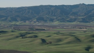 AX70_111 - 4K stock footage aerial video Green hills and farms with mountains in the background in Hollister, California