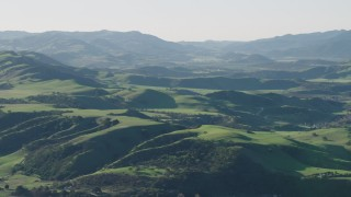 AX70_114 - 4K stock footage aerial video Approaching green hills in Hollister, California