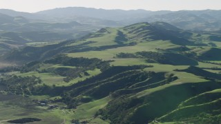AX70_115 - 4K stock footage aerial video Flyby green hills in Hollister, California