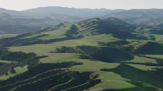AX70_116 - 4K stock footage aerial video Approach green hills in Hollister, California