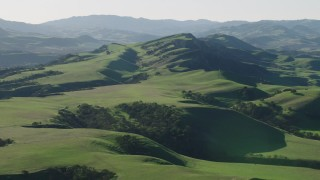 AX70_117 - 4K stock footage aerial video An approach to green hills in Hollister, California