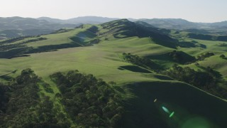 AX70_118 - 4K stock footage aerial video Flying over green hills and trees in Hollister, California
