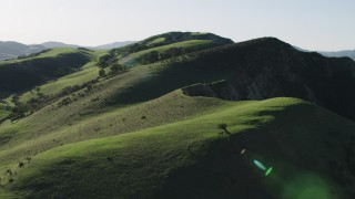 AX70_121 - 4K stock footage aerial video Flying over green hilltops in Hollister, California