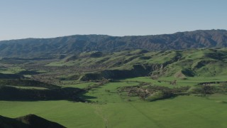AX70_125 - 4K stock footage aerial video Fly over a green hill to reveal a valley and mountains in Hollister, California