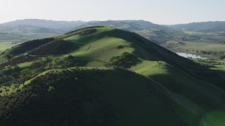 AX70_129 - 4K stock footage aerial video Approach the top of a green hill in Hollister, California