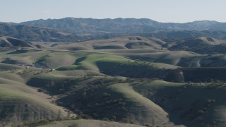 AX70_168 - 4K stock footage aerial video Passing green hills with trees in San Benito County, California