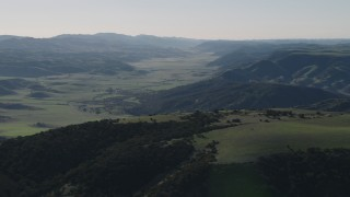 AX70_171 - 4K stock footage aerial video of A valley surrounded by green hills in San Benito County, California