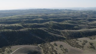 AX70_176 - 4K stock footage aerial video Flying over green hills crossed by dirt roads in San Benito County, California