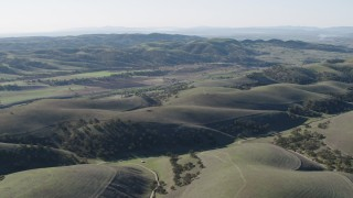 AX70_180 - 4K stock footage aerial video Approach small farms from the hills in San Benito County, California