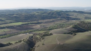 AX70_181 - 4K stock footage aerial video Approach small farms and green hills in San Benito County, California