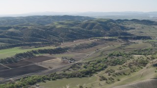 AX70_182 - 4K stock footage aerial video An approach to small farms and green hills in San Benito County, California